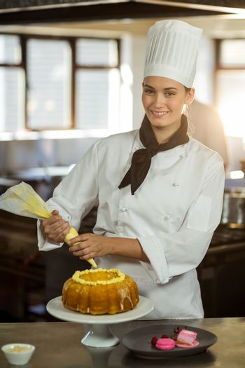 Portrait of female chef piping icing on cake