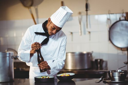 Chef sprinkling pepper on a meal