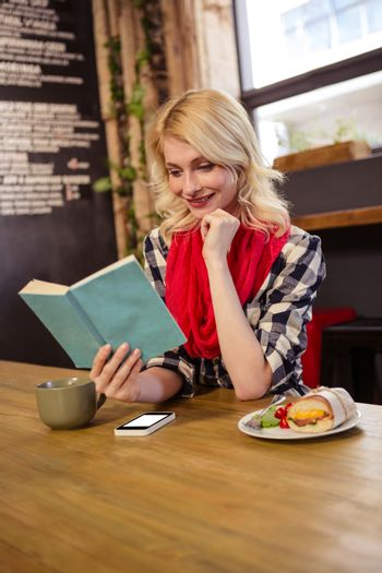 Young woman reading novel in cafeteria