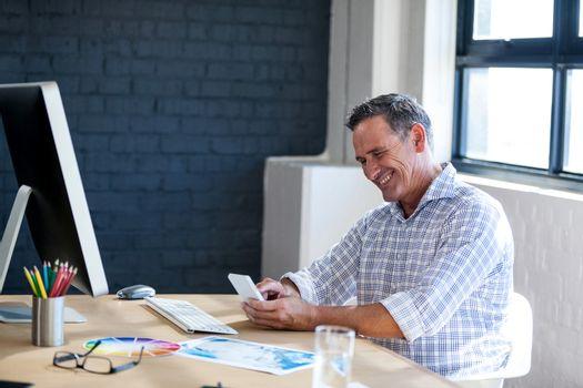 Businessman smiling and using a mobile phone