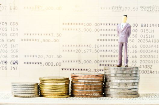 Miniature businessman stand on the stack of coins on book bank background with light. Financial concept.