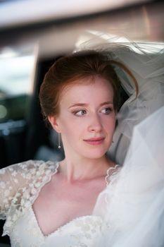 Portrait of a beautiful bride in a car