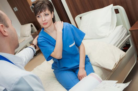 A doctor is performing exam of a patient with shoulder pain in hospital.
