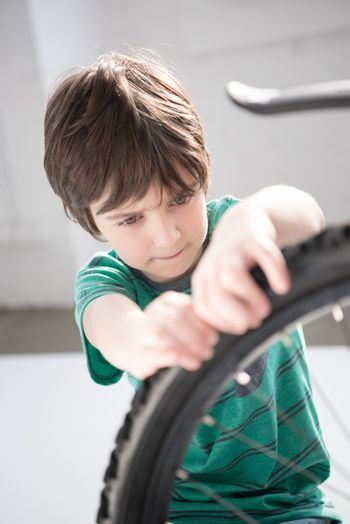 Concentrated little boy checking bicycle tyre indoors