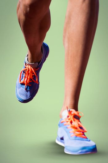 Close up of sportsman legs walking on a white background against green background