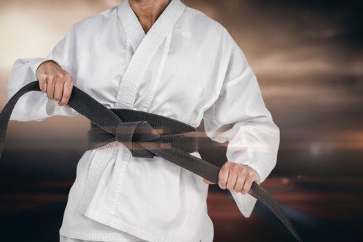 Composite image of female athlete tightening her judo belt