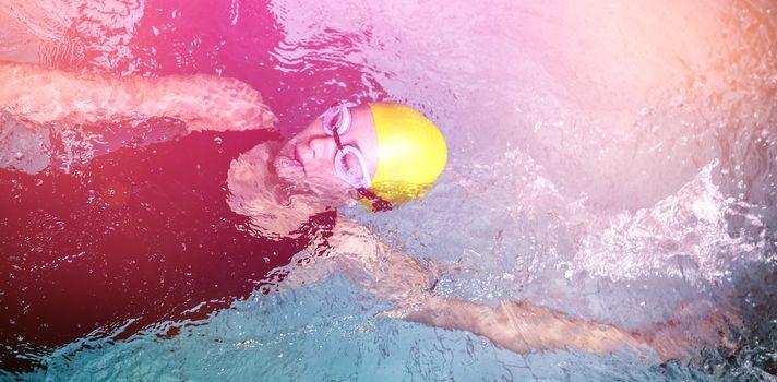 Fit female swimmer doing the back stroke