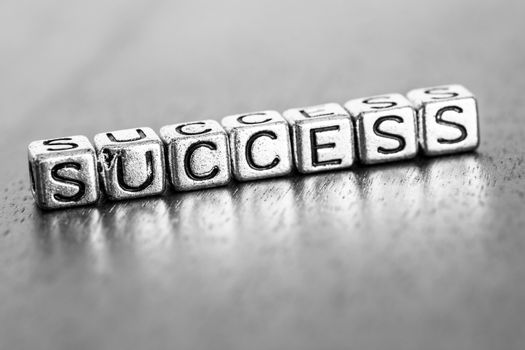 success letters placed on a desk in precious wood