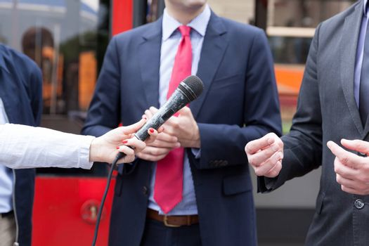 Reporter holding microphone, conducting press interview. News conference.