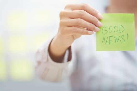 Woman holding sticky note with Good news text