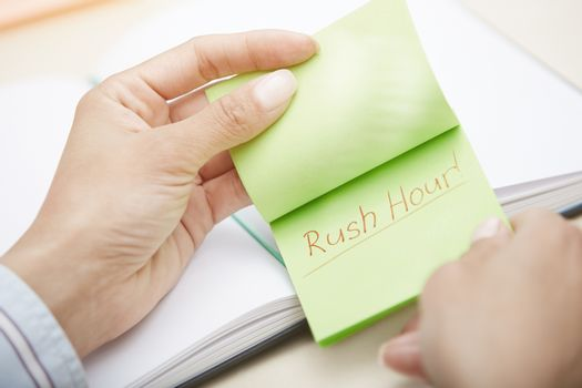 Hands holding pink sticky note with Rush hour text
