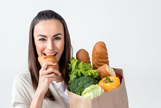 portrait of woman with grocery bag biting bread on white