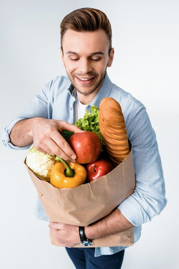 Handsome smiling man holding grocery bag on white