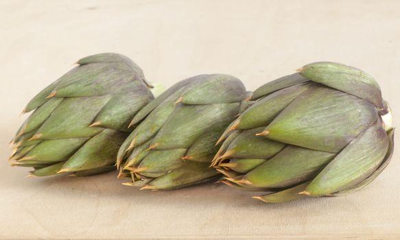 Italian raw artichokes on a wooden board