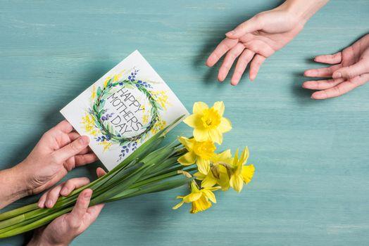 Man presenting card and daffodils