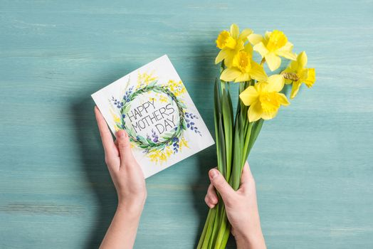 Card and daffodils in hands