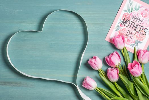 Beautiful pink tulips with happy mothers day greeting card and heart shaped ribbon