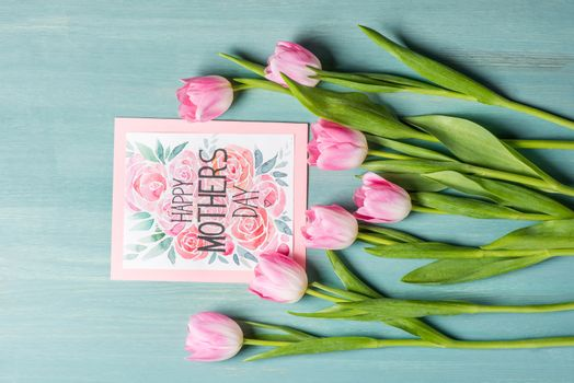 Top view of beautiful pink tulips and happy mothers day greeting card