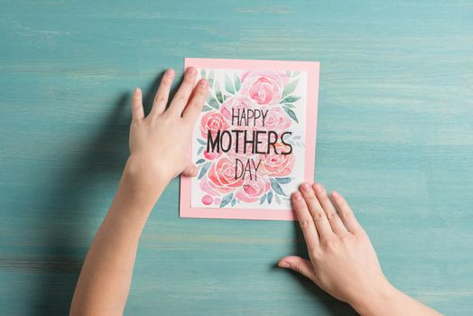 Close-up top view of happy mothers day greeting card in hands