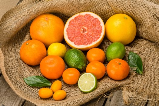 Close-up view of various whole and sliced fresh citrus fruits on sackcloth