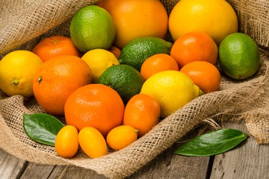 Close-up view of various fresh ripe citrus fruits on sackcloth
