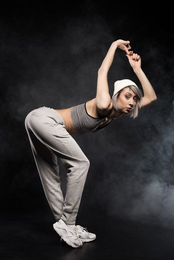 side view of woman in sports clothing dancing on black