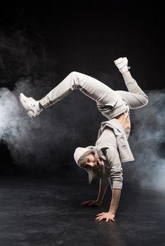 woman in sports clothing break dancing on black