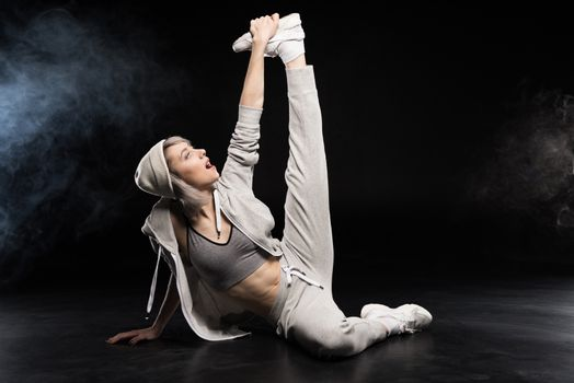 woman in sports clothing stretching on black