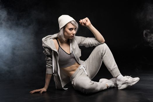 woman in sports clothing sitting on floor on black