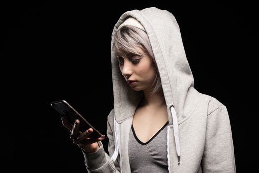 portrait of focused woman in sports clothing using smartphone