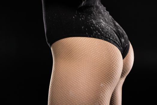partial view of woman in bodysuit on black