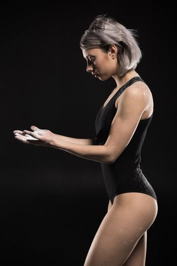 side view of woman in bodysuit with dust on black