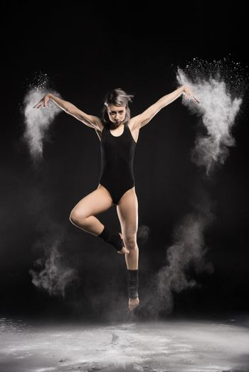 concentrated woman in bodysuit with dust jumping on black