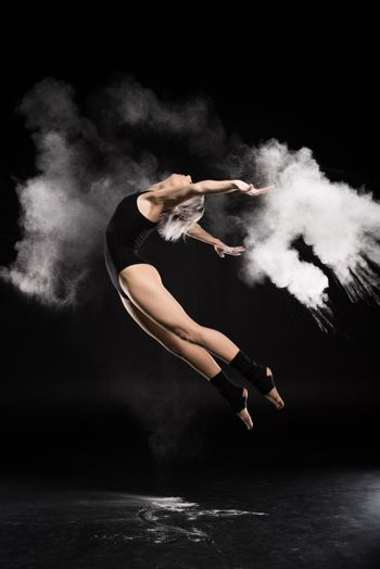 side view of woman in bodysuit with dust jumping on black
