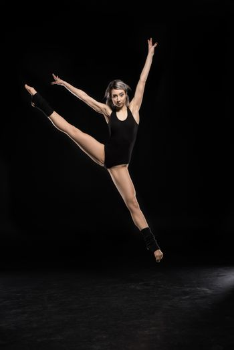 beautiful jumping woman in bodysuit on black