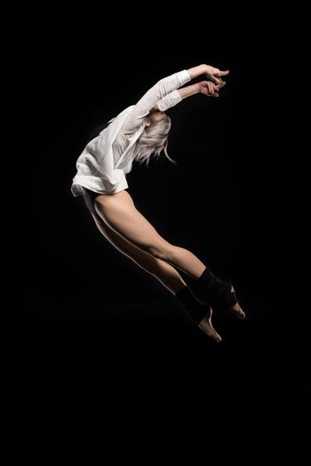 side view of jumping woman in bodysuit on black