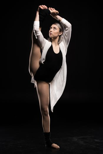 woman in bodysuit stretching before dancing on black