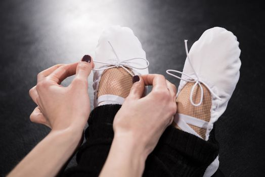 Close-up partial view of woman dancer tying ballet shoes on black
