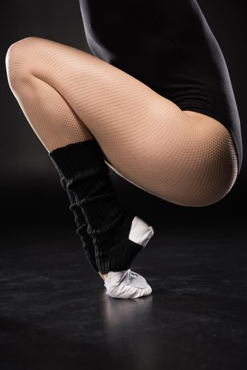 Partial view of young woman dancer in sportswear training on black