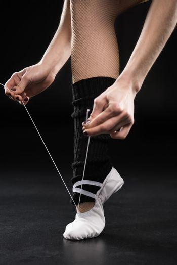 Close-up partial view of woman dancer tying ballet shoe on black