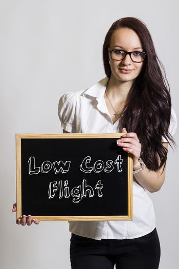 Low cost Flight - Young businesswoman holding chalkboard - vertical image
