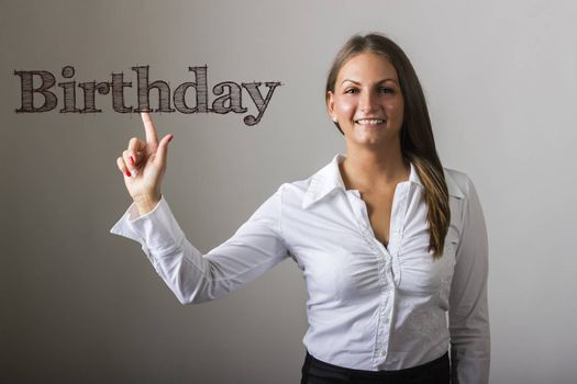 Birthday - Beautiful girl touching text on transparent surface - horizontal image