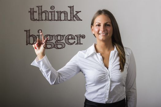Think Bigger - Beautiful girl touching text on transparent surface - horizontal image