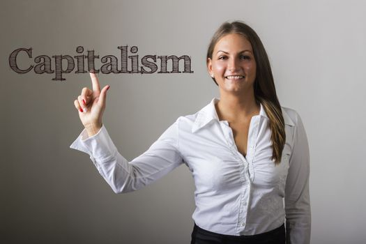 Capitalism - Beautiful girl touching text on transparent surface - horizontal image