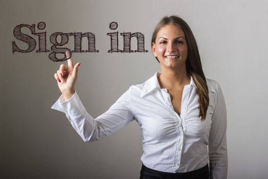 Sign in - Beautiful girl touching text on transparent surface - horizontal image