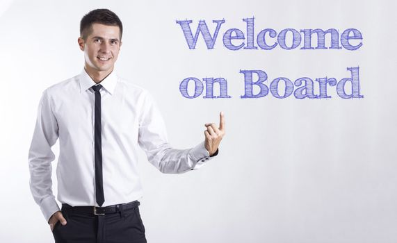 Welcome on Board - Young smiling businessman pointing on text - horizontal images