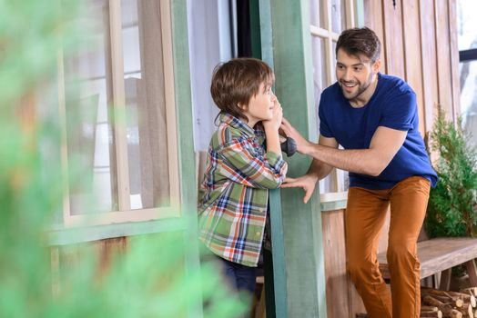 side view of smiling man and boy playing hide and seek at home
