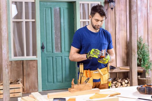 portrait of carpenter regulating tool for woodworking on porch