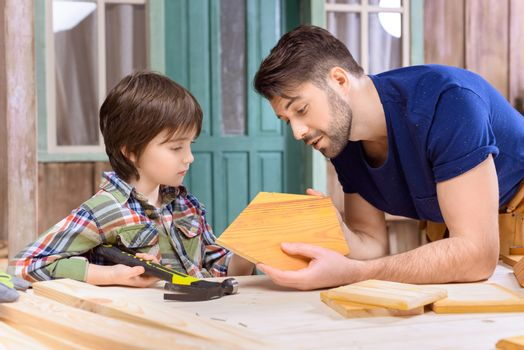 Side view of father and son woodworking together in workshop