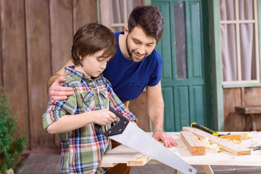 Smiling father looking at concentrated son sawing wooden plank